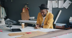 African American man designer writing in notebook working in studio alone. African American man fashion designer is writing in notebook with pencil working in stock footage