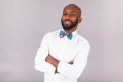 African American man with folded arms wearing a bow tie. African American young man with folded arms wearing a bow tie Royalty Free Stock Image