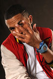 African American Man Gesturing. Portrait of young African American hip hop man with hand in front of face Stock Photos
