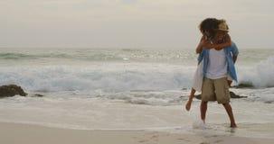 African american man giving piggyback ride to woman on the beach 4k. African american man giving piggyback ride to woman on the beach. They are having fun 4k stock video