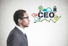 African American man glasses, CEO. Side view of a young handsome African American businessman wearing glasses and a gray suit. A concrete wall background with a stock image
