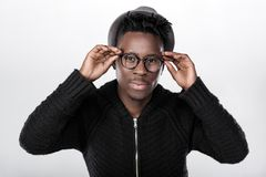 African-American man in glasses. Portrait of a young African-American man in glasses on a gray background Royalty Free Stock Images