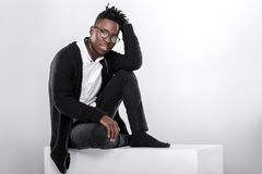 African-American man in glasses. Portrait of a young African-American man in glasses looking at camera on gray background Stock Photo