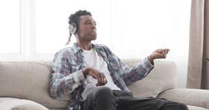 Young man having fun while listening music on headphones. African american man having fun while listening music on headphones stock video