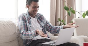 Happy man during video chat on laptop. African american man having fun while video conferencing on laptop at home stock video