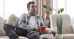 Man having fun watching tv and having breakfast. African american man having fun watching tv and having breakfast on sofa in the living room stock video footage