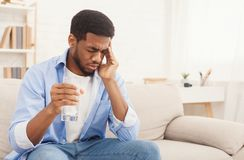 African-american man with headache taking pill at home. Exhausting headache. Sick african-american man taking pill with glass of water, suffering from migraine stock image
