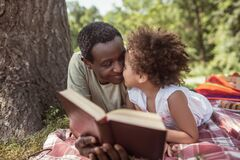 African american man and his cute kid reading a book together
