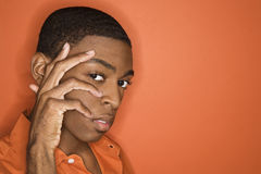 African-American man with his hand on his face. Young African-American man with hand on his face on orange background Royalty Free Stock Image