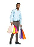 African american man holding shopping bags on white. Holidays co Royalty Free Stock Photo