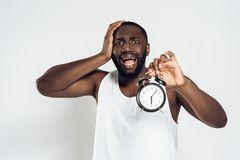 African American man holds head with alarm clock royalty free stock images