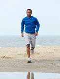 African american man jogging at beach Stock Images