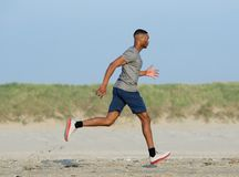 African american man jogging at the beach Royalty Free Stock Photography