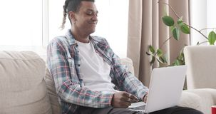 Man having fun using laptop at home. African american man laughing while using laptop on sofa at home stock footage
