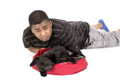 African American man laying by his labrador puppy Stock Image