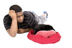 African American man laying with his puupy dog Stock Image