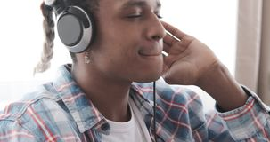Young man listening music on headphones. African american man listening music on headphones at home stock video footage