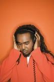 African-American man listening to headphones. African-American mid-adult listening to headphones wearing orange clothing on orange background Stock Photos