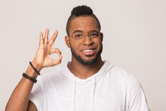 African American man make hush gesture isolated in studio. Millennial african American man wearing glasses isolated on grey studio background look at camera make royalty free stock images