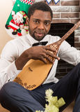 African American man with Musical instrument Dombra by fireplace. Christmas Stock Photography