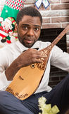 African American man with Musical instrument Dombra by fireplace. Christmas Royalty Free Stock Photos