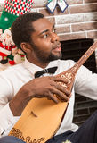 African American man with Musical instrument Dombra by fireplace. Christmas Stock Images