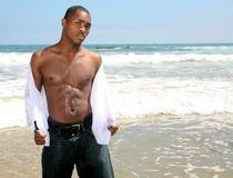 African American Man Opening His Shirt in the Surf Royalty Free Stock Photo