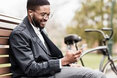 African-american man with phone sitting on bench near bicycle