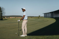African american man playing golf on golf course at daytime. Stylish african american man playing golf on golf course at daytime Royalty Free Stock Photo