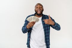 African-American man pointing finger into bunch of dollars, capital investment.  stock photography