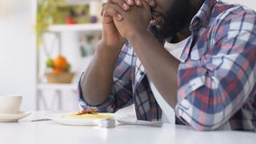 African american man praying before eating, asking god to bless food, faith