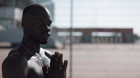 African American man praying to God on the street and looking into the camera. Concept of faith, religion, poverty