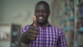 African American man raises his thumb up in library. African American man shows big finger to the camera in library. The male is happy and smiles wide. Portrait stock footage