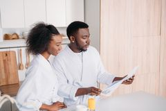 African american man reading newspaper and smiling girlfriend stock images