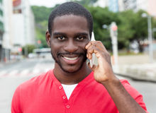 African american man with red shirt at phone in city Royalty Free Stock Image