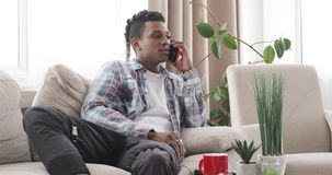 Young man watching tv and talking on mobile phone at home. African american man relaxing on sofa while watching tv and talking on mobile phone stock footage
