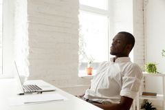African-american man relaxing after work breathing air in home o. African american man relaxing after work breathing fresh air sitting at home office desk with Stock Photography