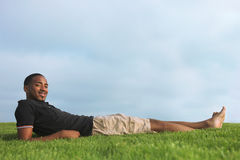 African American Man Resting in Green Grass Royalty Free Stock Photos