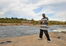 African American man in Richmond, VA. Muscular African american man wearing chains standing on the rocks of a river Stock Images