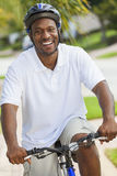 African American Man Riding Bicycle. A happy African American man riding his bicycle outside wearing shorts, helmet and polo t-shirt royalty free stock photo