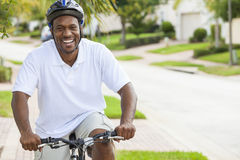 African American Man Riding Bicycle. A happy African American man riding his bicycle outside wearing shorts, helmet and polo t-shirt royalty free stock photos