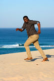 African American man running away. Full body side view of a black young man running away in shoes on the beach in sunny weather Royalty Free Stock Photos