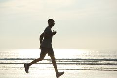 African american man running on beach Stock Photos