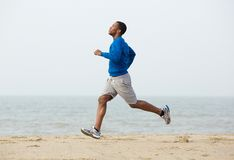 African american man running at the beach Royalty Free Stock Photos