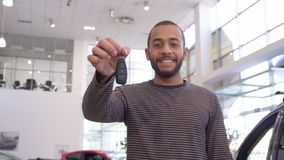 Man shows car key at the dealership. African american man showing car key at the dealership. Handsome bearded male customer smiling for the camera at the Royalty Free Stock Image