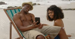African american man showing photos to woman on mobile phone at beach 4k. African american man showing photos to woman on mobile phone at beach. They are stock video footage