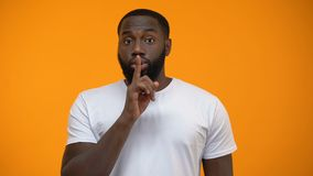 African-American man showing silence gesture, keeping secret, yellow background. Stock footage stock footage