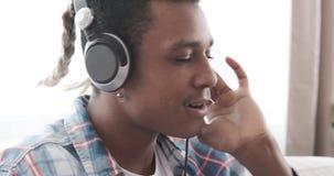 Man singing and listening music on headphones at home. African american man singing and listening music on headphones at home stock video