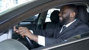 African American man sitting in expensive car satisfied and smiling, test drive royalty free stock image