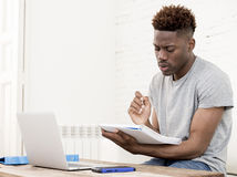 African american man sitting at home living room working with laptop computer and paperwork Royalty Free Stock Photo